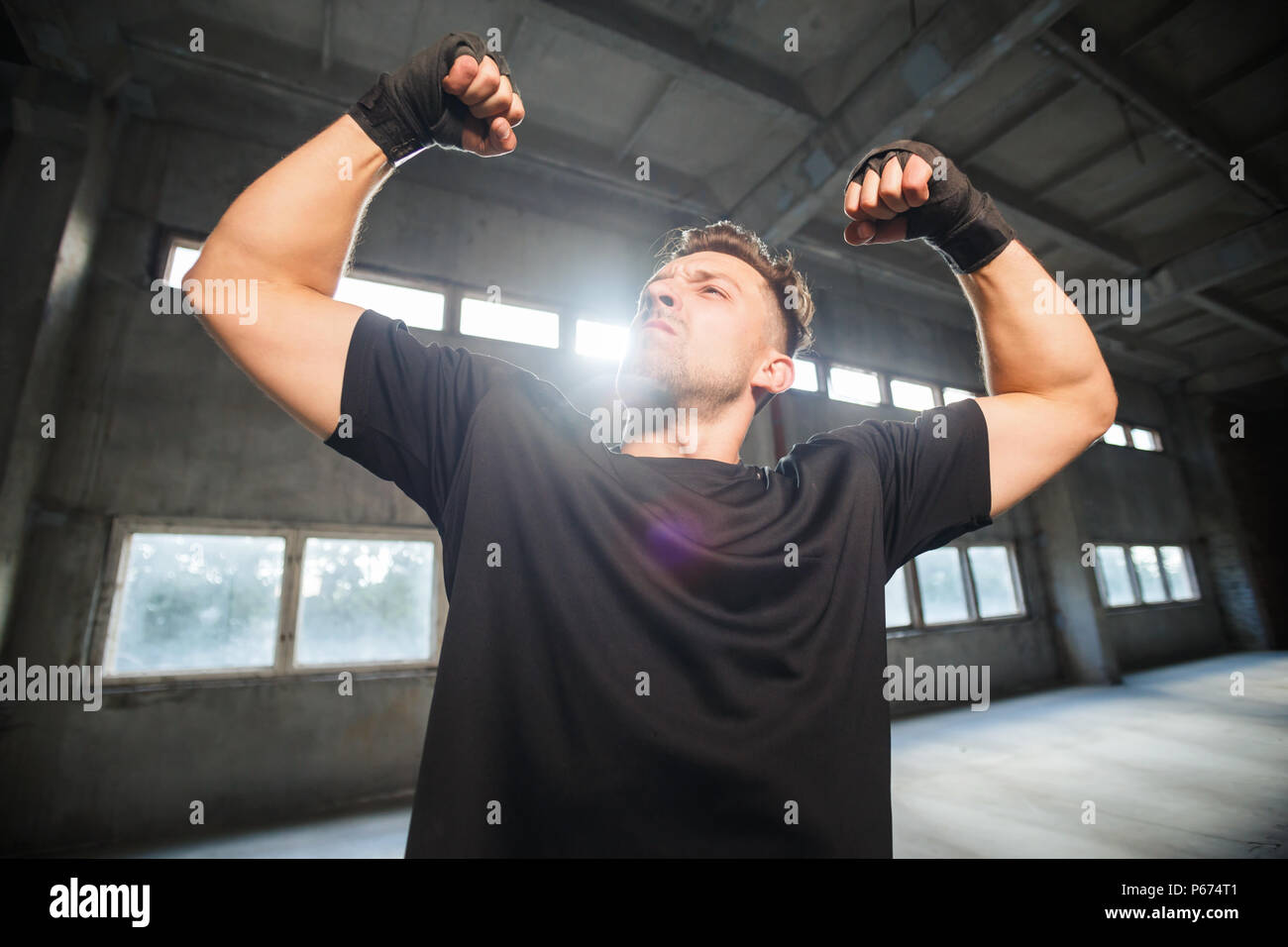 Thai boxer dressed in black t-shirt shows biceps power, fists with black bandages around at empty industrial dusty place - Stock Image