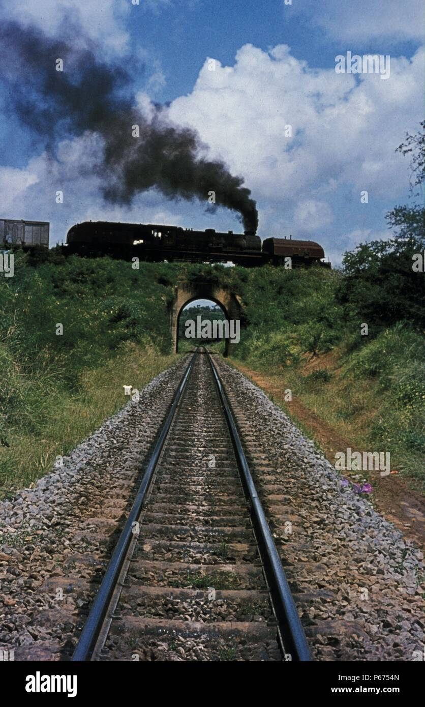 The Mombasa Spiral. East African Railway's 59 Class 2-8-4+4-8-2 Garratt No.5922 'Mount Blackett' climbs inland from Mombasa on the Indian Ocean. These - Stock Image