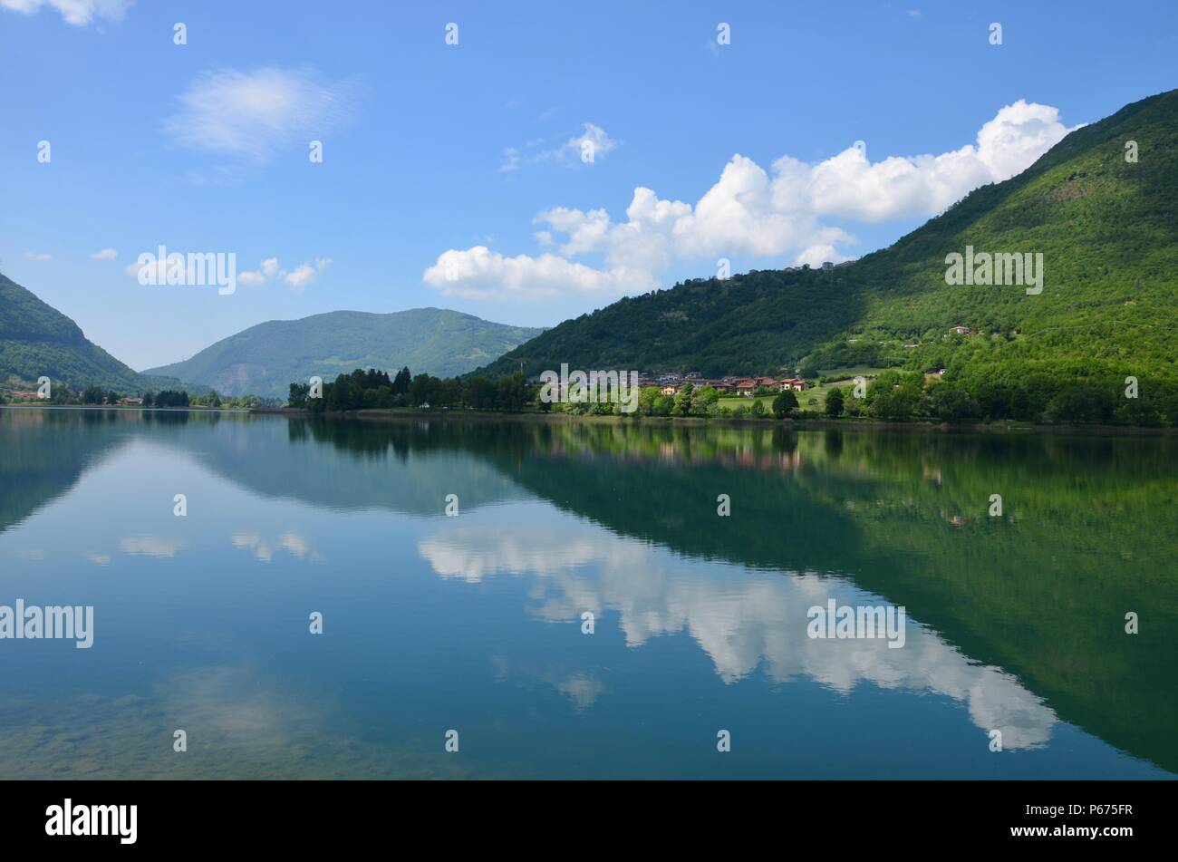 Lago d'Iseo in Lombardy in Italy, sea view, tourism, water surface, lake, summer, blue sky, boat rides, clouds, hills, climbing, hiking trails, sun - Stock Image