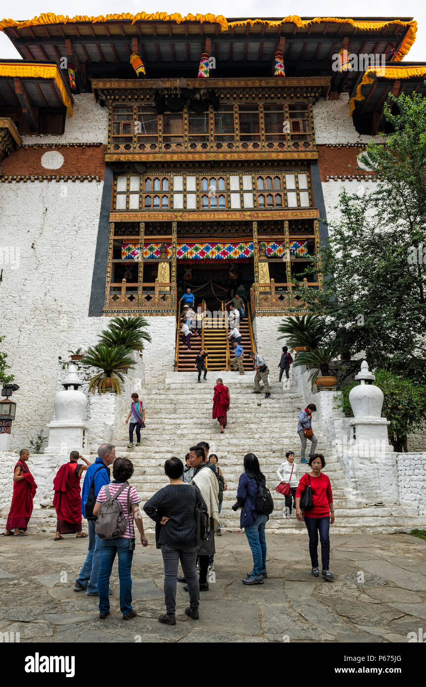 Punakha, Bhutan - April 10, 2016: Unidentified biddhist monks and vistors with traditional robes are entering and leaving the Punakha Dzong or Pungtha - Stock Image