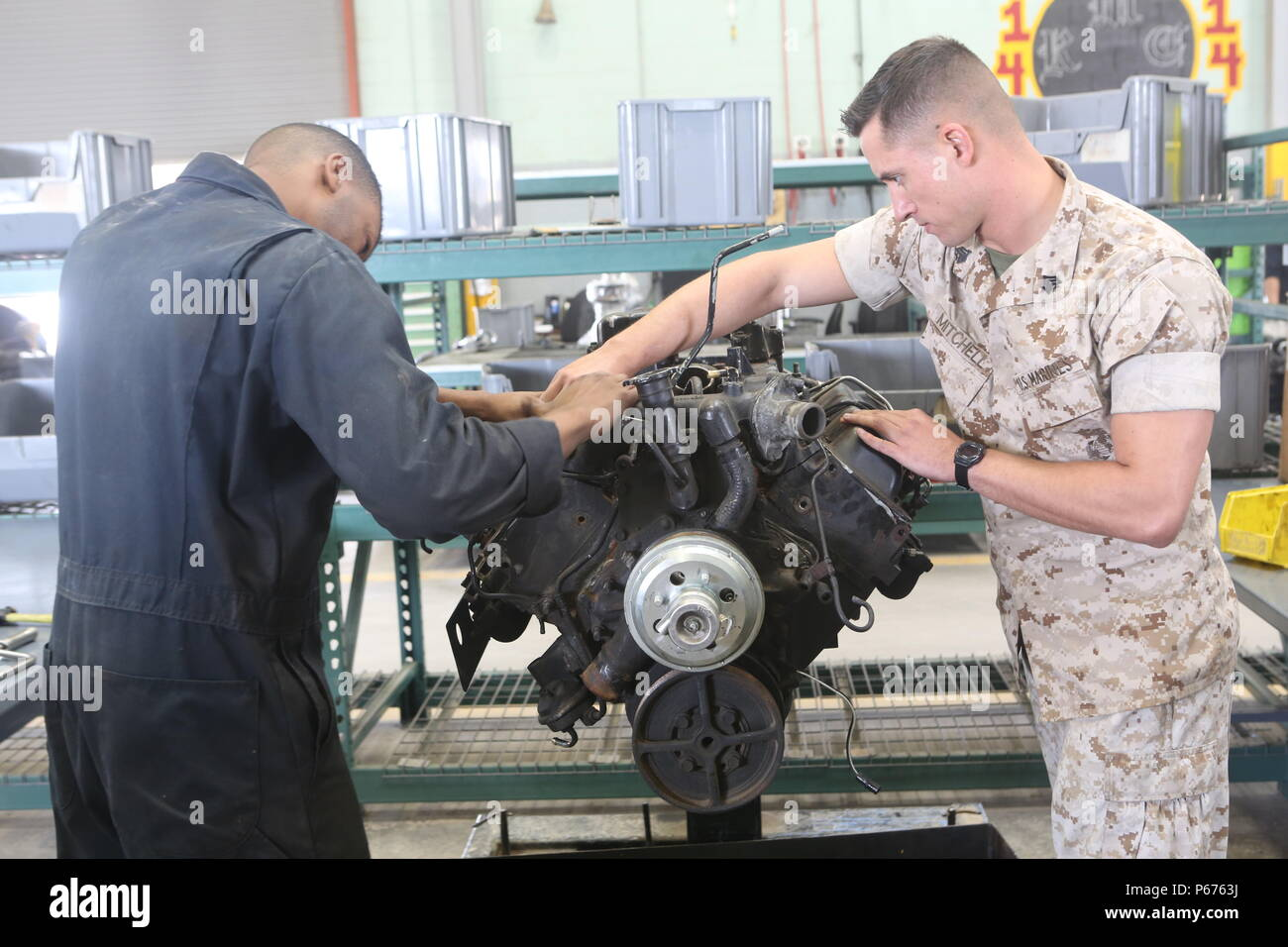 U.S. Marine Corps Cpl. Adonis Stark and Sgt. Phillip Mitchell with Combat Logistics Regiment (CLR) 15, Repairable Maintenance Company, work together to repair a 6.5L Turbo Diesel Engine during a Marine Logistics Group (MLG) Day event on Camp Pendleton, Calif., May 18, 2016. The purpose of MLG Day is to showcase the capabilities of the 1st MLG to new officers and international military visitors.(U.S. Marine Corps photo by Lance Cpl. Salmineo Sherman Jr. Combat Camera 1st MLG/ RELEASED) - Stock Image