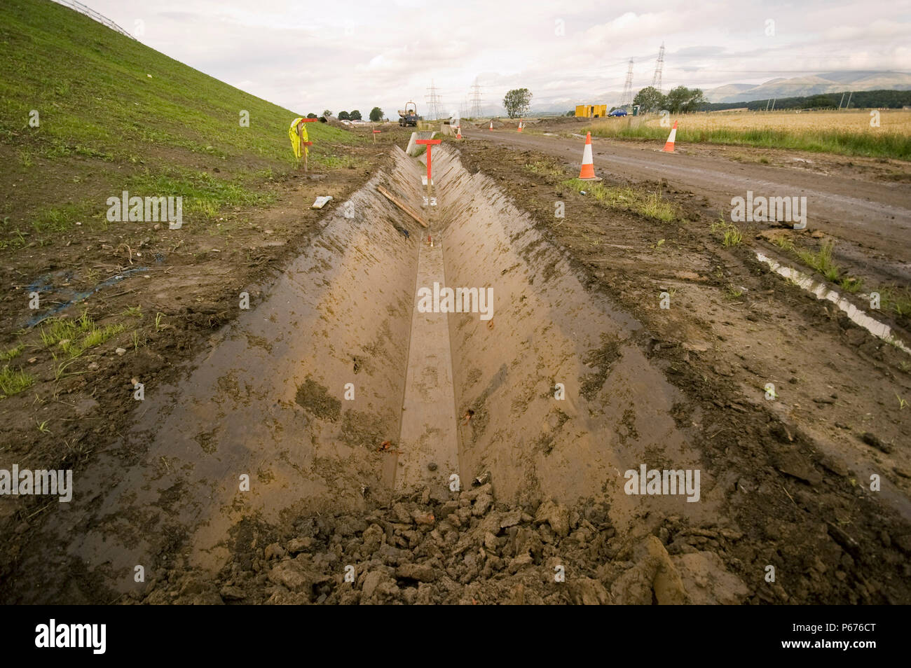 Drainage ditch dug out by a trapezoidal excavator bucket - Stock Image