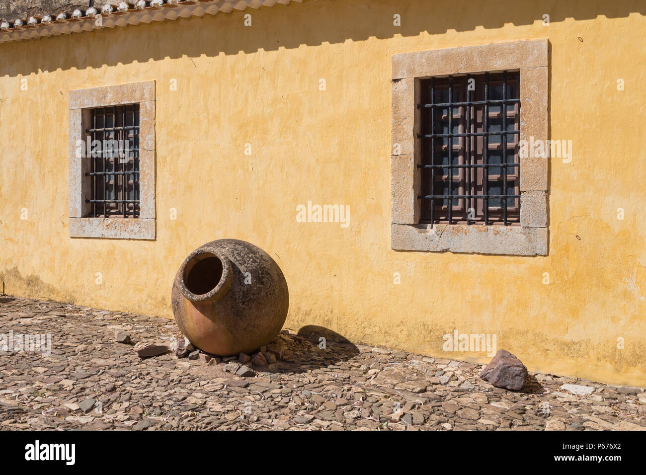 Yellow wall of an old house, part of Castro Marim castle. Windows ...