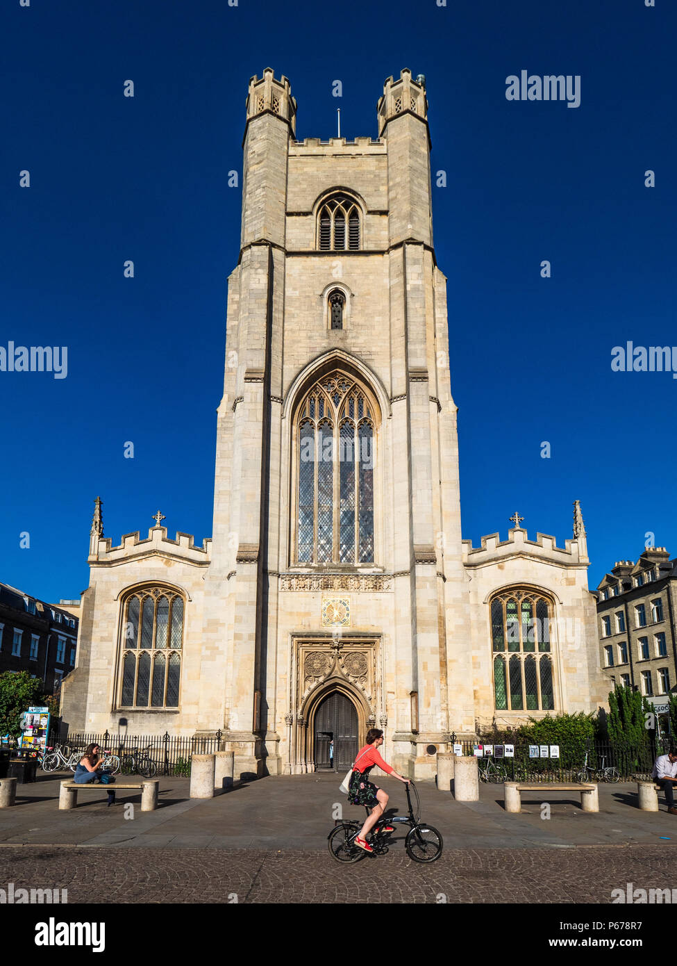 Cambridge Tourism - cyclists pass Great St Mary church in central Cambridge. The church, rebuilt after a fire in 1290, is Cambridge University Church - Stock Image