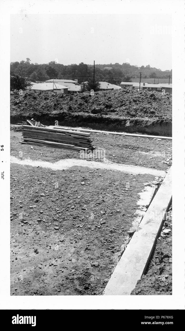 Black and white photograph, showing a construction site, with the outline of a concrete foundation, dirt, and lengths of wood, with the roofs of houses visible in the background, likely photographed in Ohio, July, 1956. () - Stock Image