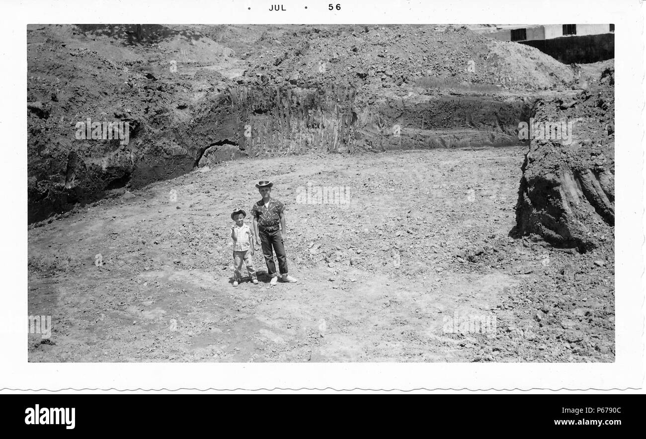 Black and white photograph, showing a man and a small boy, both wearing wide-brimmed hats, standing next to each other in the midst of a rocky construction site, surrounded with mounds of dirt, likely photographed in Ohio, July, 1956. () - Stock Image