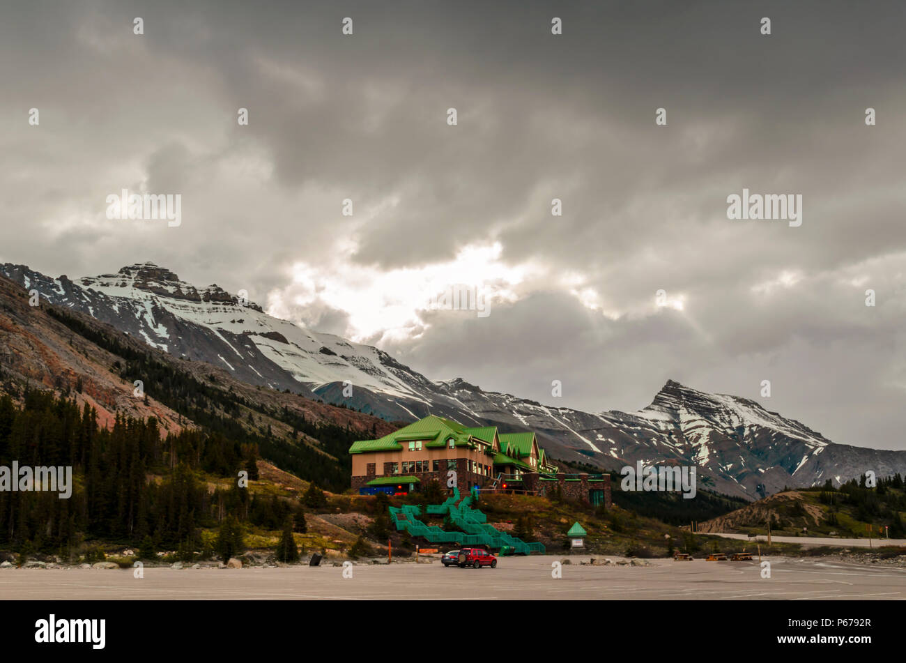 Parking for cars with two cars at the foot of the mountains and buildings with green staircases and a green roof, coniferous trees and snow - Stock Image