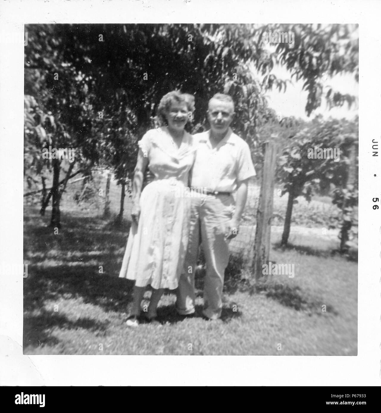 Black and white photograph, showing an older couple, both smiling, standing outdoors in full length, the man wears a light colored shirt and trousers, and wraps his arm around the waist of his wife who wears a light colored, tea-length dress, with foliage visible in the background, likely photographed in Ohio, June, 1956. () Stock Photo
