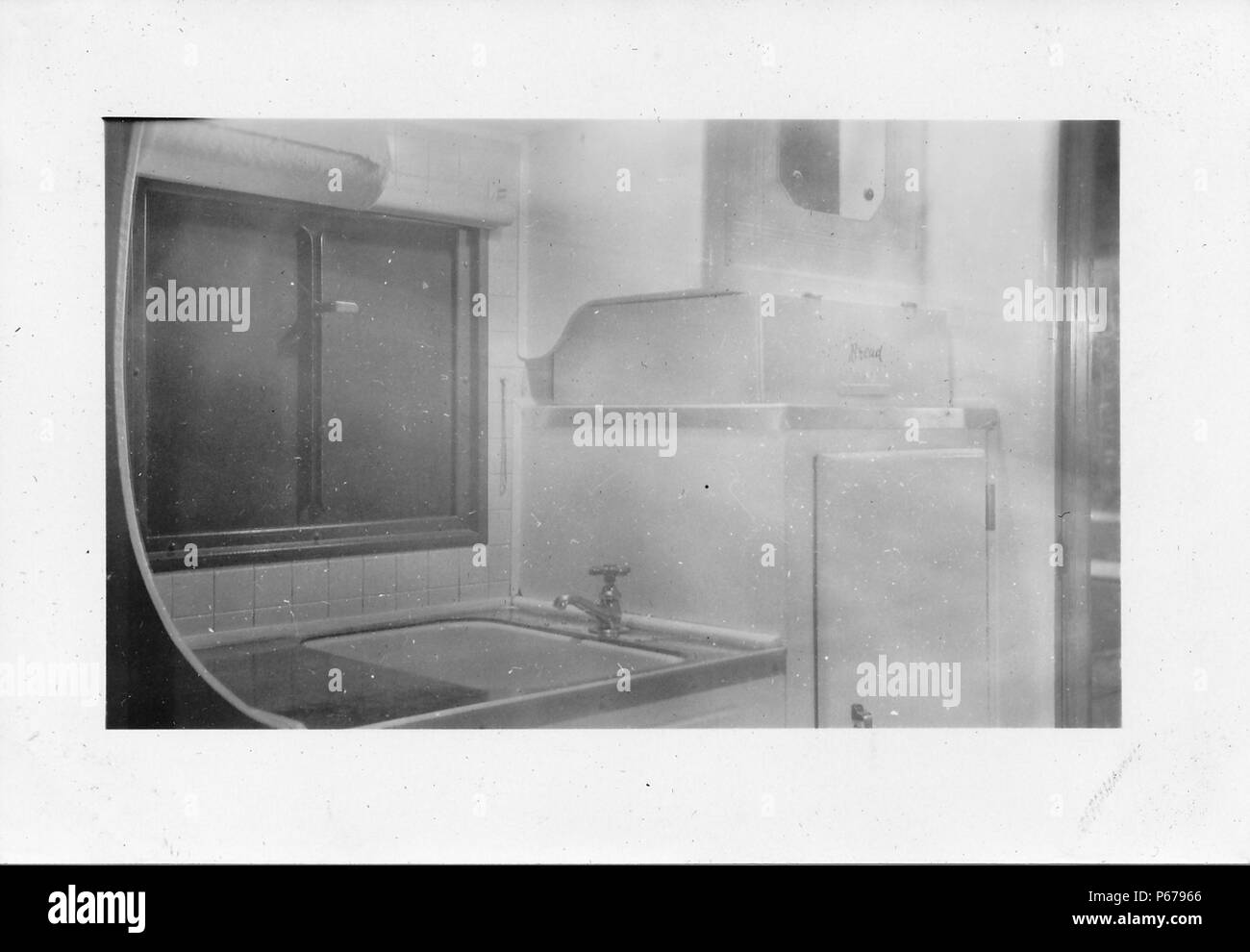 Black and white photograph, showing a small, partially tiled kitchenette located in the cramped interior of a Mid-century caravan or trailer home, with a sink, refrigerator, and window, likely photographed in Ohio in the decade following World War II, 1950. () - Stock Image