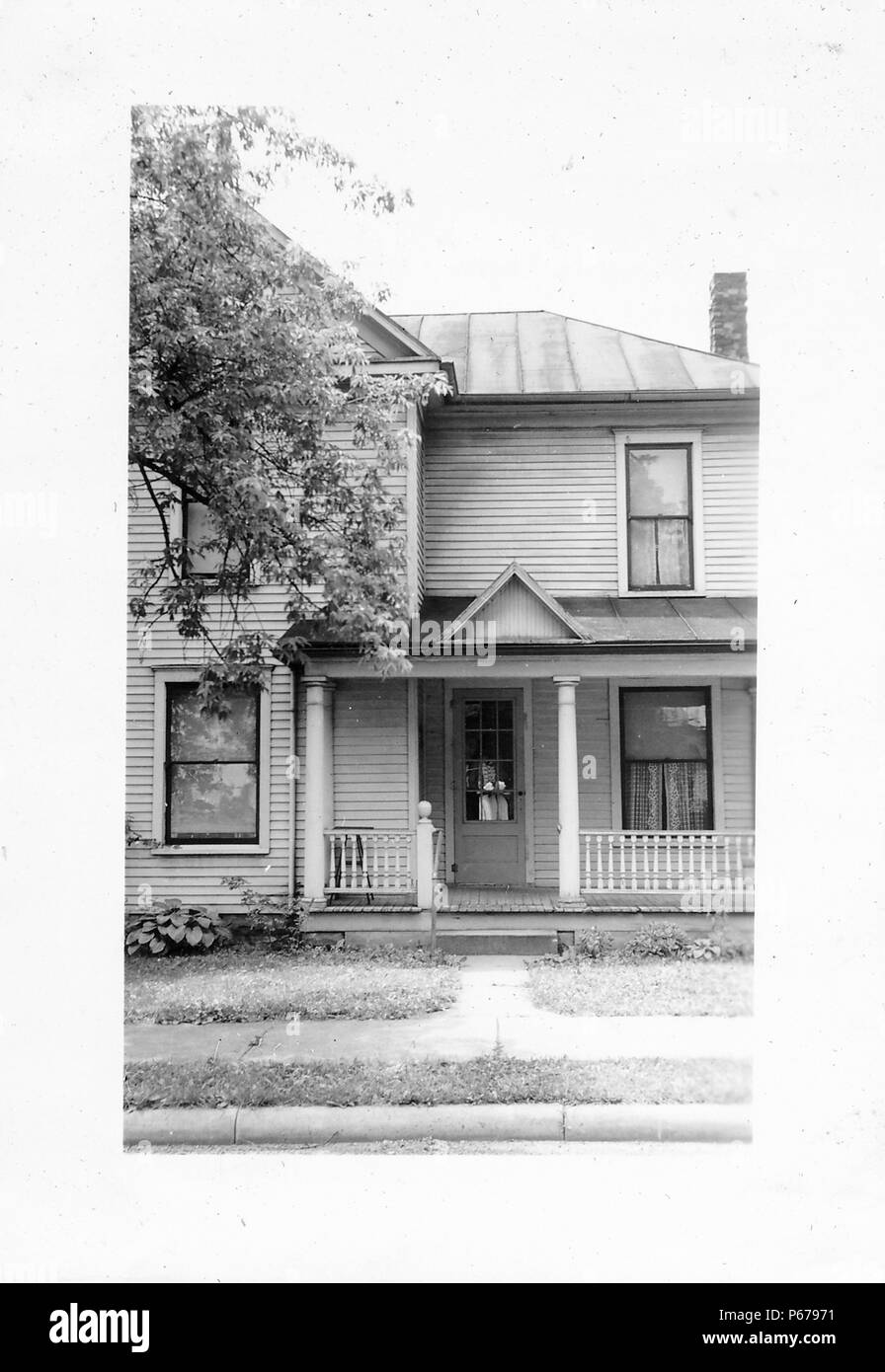 Black and white photograph, showing the front of a small, light-colored, wooden house, with a covered front porch, with Doric columns and a small gable over the entrance, likely photographed in Ohio in the decade following World War II, 1950. () - Stock Image