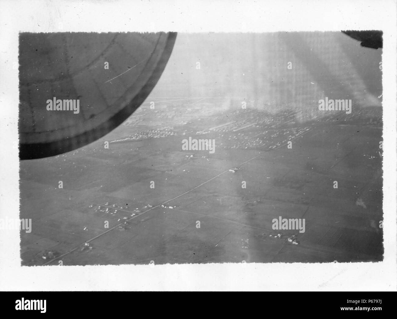 Black and white photograph, shot from the interior of an airplane in flight, looking down on rectangular patches of flat, partially cultivated, partially populated land, with part of the engine visible in the upper foreground, likely photographed during World War II, 1945. () - Stock Image