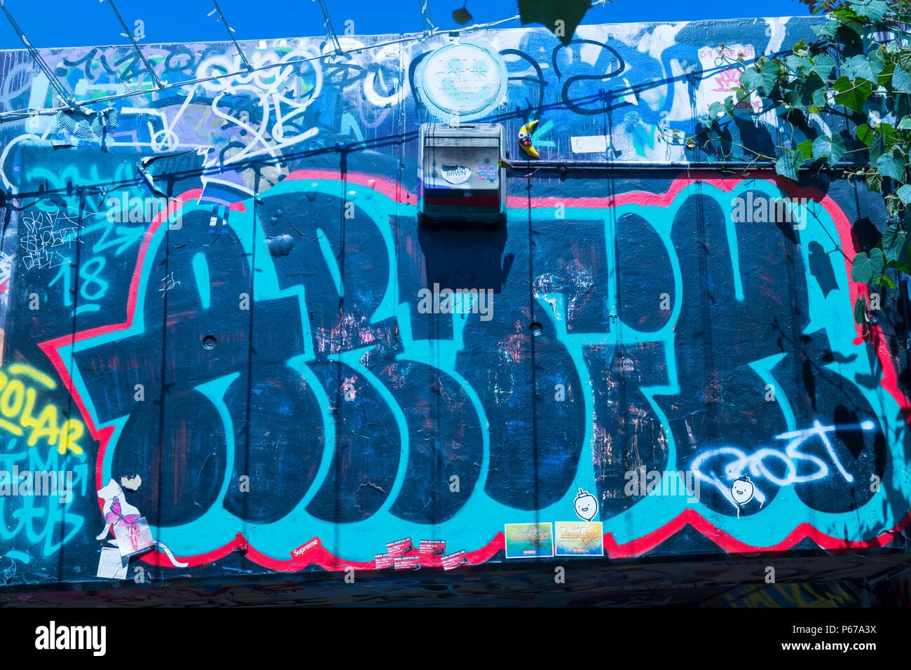 London Waterloo Leake Street graffiti light dark blue letters script wall pavement sidewalk detail Arthur blue sky leaves - Stock Image