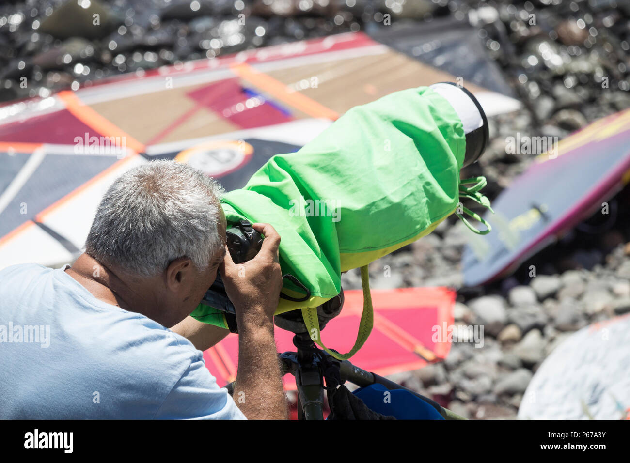 Sport photographer protecting camera and lens from sea spray - Stock Image