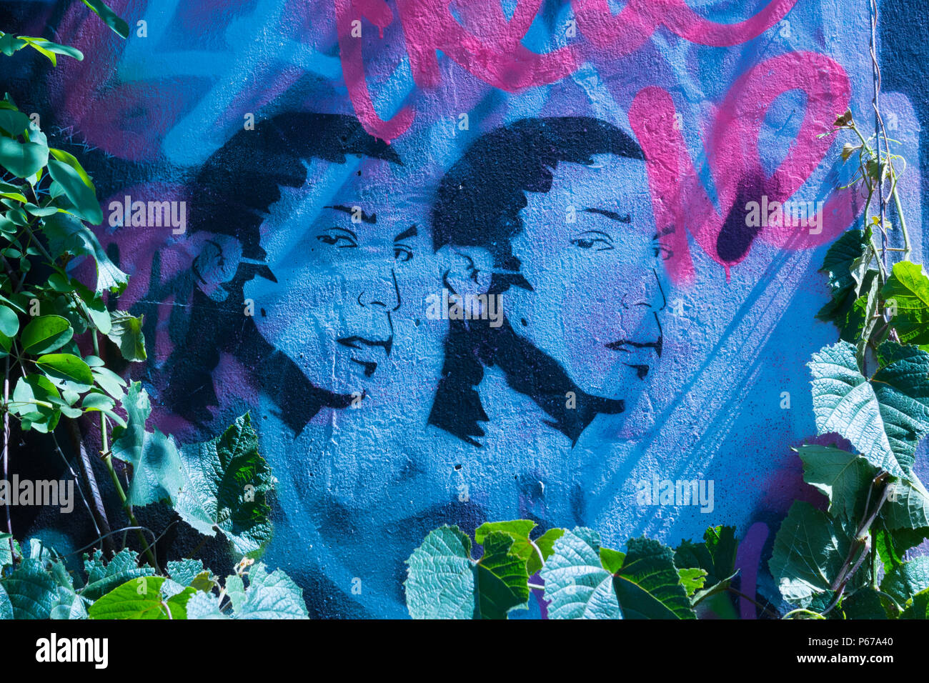London Waterloo Leake Street graffiti blue 2 two ethnic heads faces leaf leaves silhouettes - Stock Image