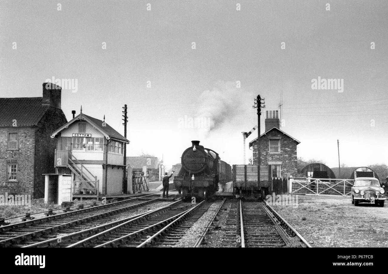 Cottam station on the direct Great Central route between Retford and Lincoln. The signalman has come down from his box to exchange the obligatory toke - Stock Image