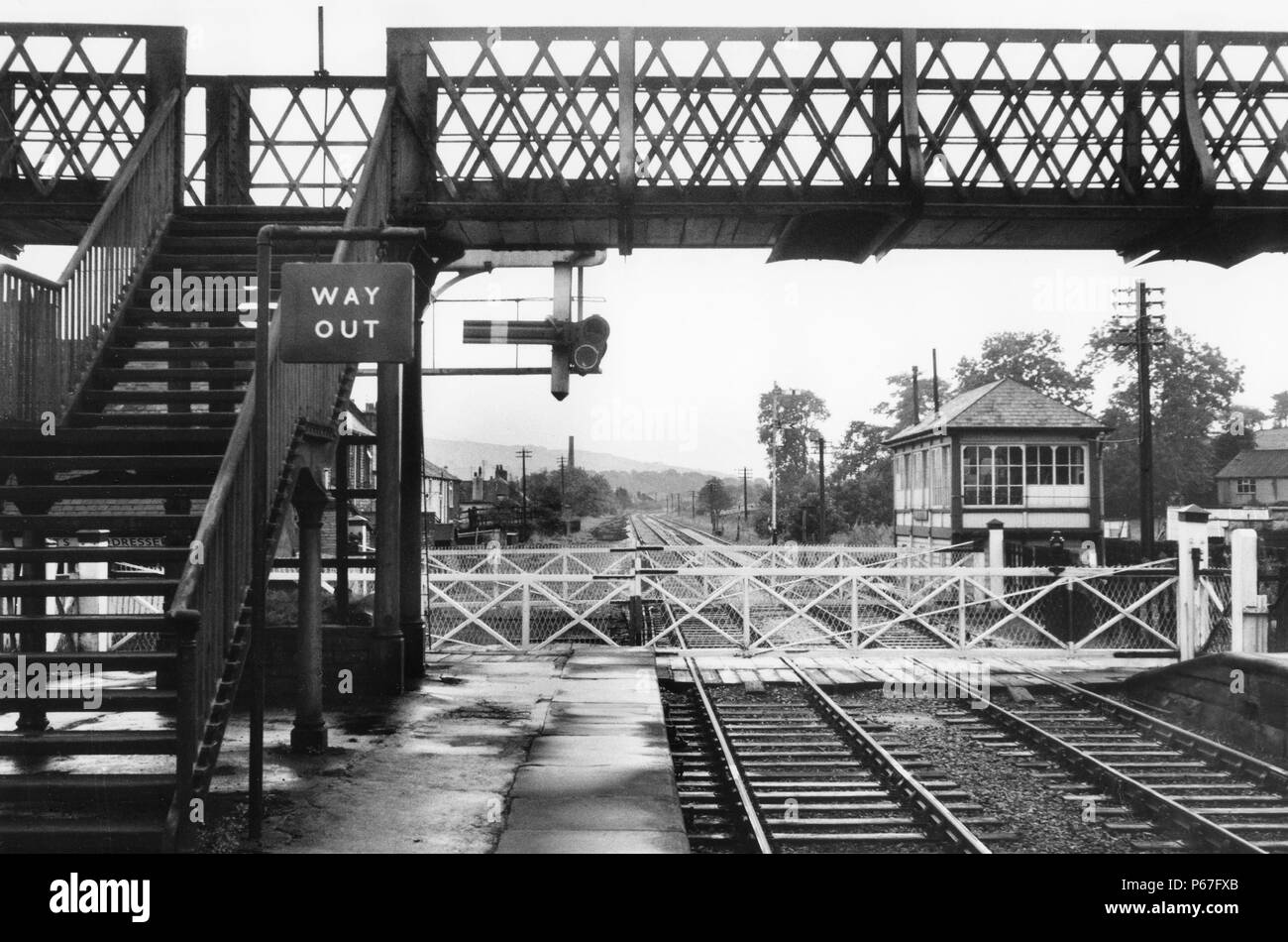 Footbridge and level crossing believed to be on Settle to Carlisle showing signal box and semaphore signals of Midland Railway origin. C 1962 - Stock Image