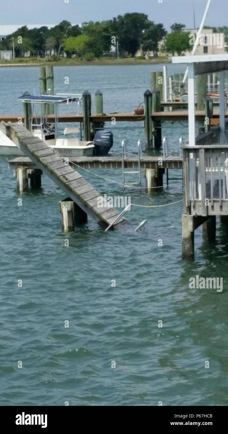 A pier hangs broken off the Spouter Inn in Beaufort, North Carolina, after the pier's fasteners broke May 11, 2016. Sanders rescued five women after a pier broke and they fell into the water. Although off-duty, Sanders leapt into the water and helped keep the women calm, escorting them to safety. (Photograph courtesy of Allison Vickers) - Stock Image