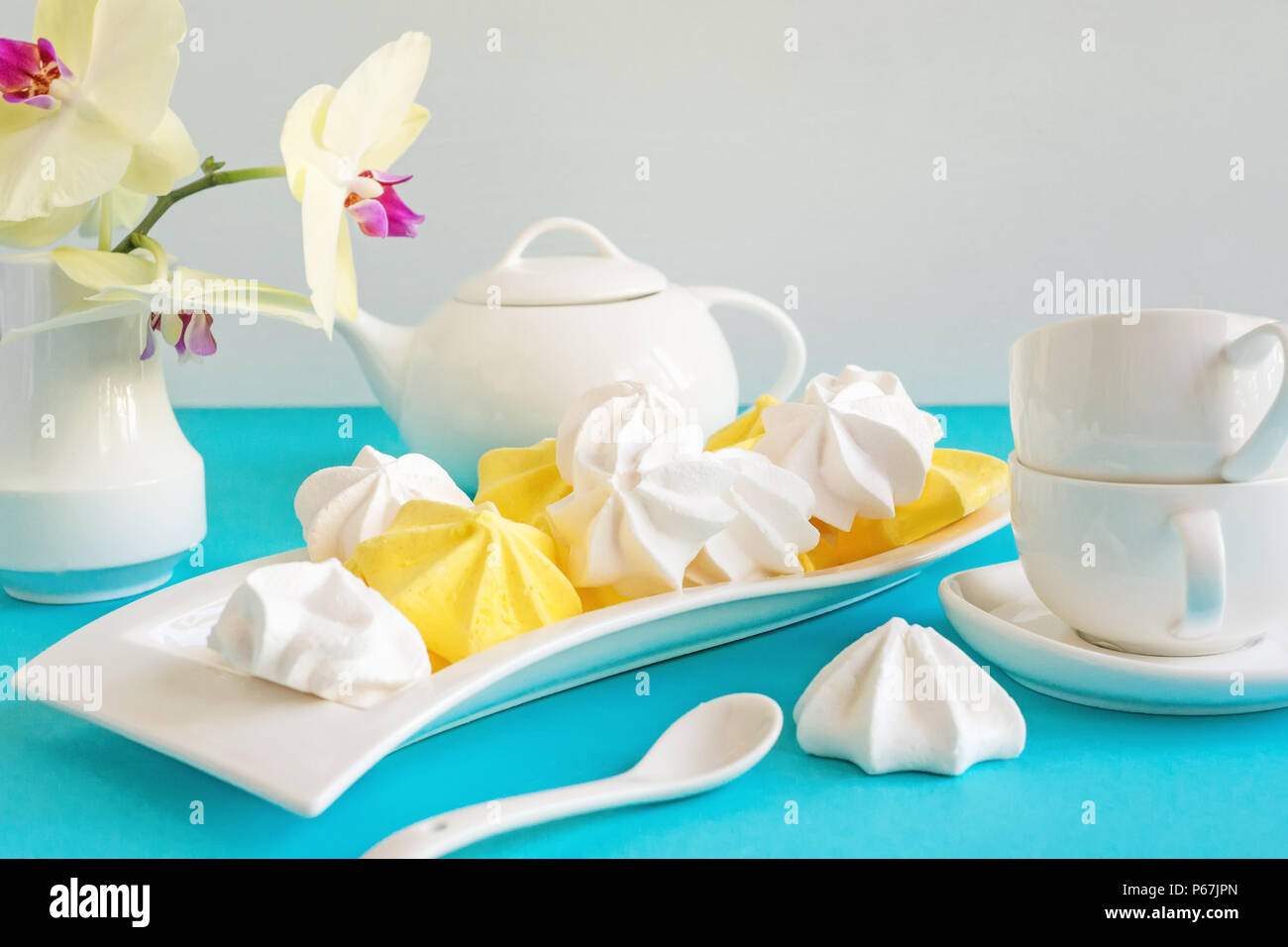 White and yellow meringue on blue background in tea serving with white kettle. Stock Photo