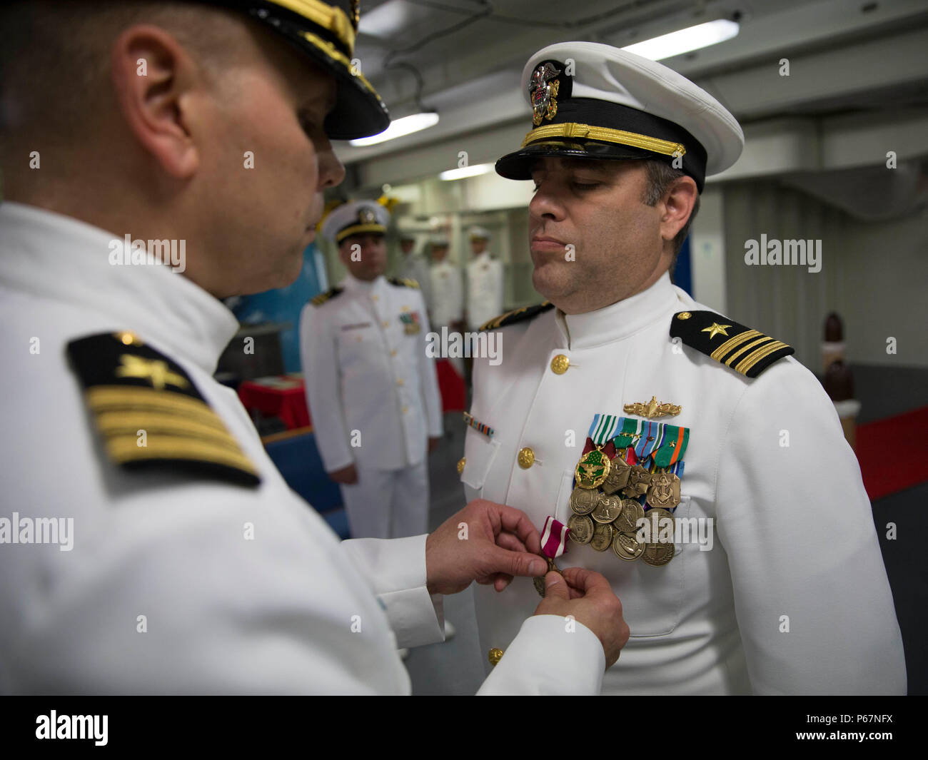 NEWPORT NEWS, Va. (May 13, 2016) --Cmdr. Allan Feenstra, chief engineer, Pre-Commissioning Unit Gerald R. Ford (CVN 78) presents Lt. Cmdr. Michael Stone with a meritorious service medal during a retirement ceremony in the ship's forecastle. Ford is the first of a new class of aircraft carriers currently under construction by Huntington Ingalls Industries Newport News Shipbuilding.  (U.S. Navy photo by Mass Communication Specialist Seaman Apprentice Connor Loessin/Released) - Stock Image