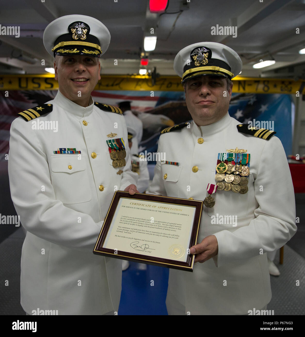 NEWPORT NEWS, Va. (May 13, 2016) --Cmdr. Allan Feenstra, chief engineer, Pre-Commissioning Unit Gerald R. Ford (CVN 78) presents Lt. Cmdr. Michael Stone with a certificate of appreciation during a retirement ceremony in the ship's forecastle. Ford is the first of a new class of aircraft carriers currently under construction by Huntington Ingalls Industries Newport News Shipbuilding.  (U.S. Navy photo by Mass Communication Specialist Seaman Apprentice Connor Loessin/Released) - Stock Image