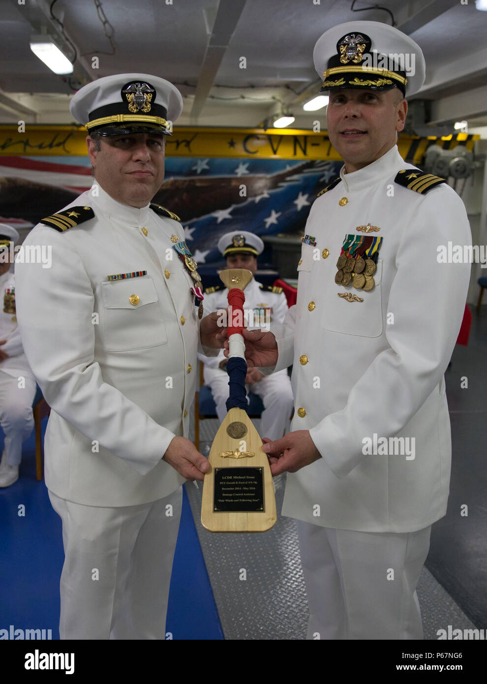 NEWPORT NEWS, Va. (May 13, 2016) -- Lt. Cmdr. Michael Stone, assigned to Pre-Commissioning Unit Gerald R. Ford (CVN 78), is presented with an oar by Cmdr. Allan Feenstra, chief engineer, during a retirement ceremony in the ship's forecastle. Ford is the first of a new class of aircraft carriers currently under construction by Huntington Ingalls Industries Newport News Shipbuilding.  (U.S. Navy photo by Mass Communication Specialist Seaman Apprentice Connor Loessin/Released) - Stock Image
