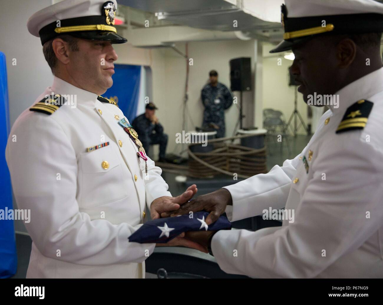 NEWPORT NEWS, Va. (May 13, 2016) – Lt. Cmdr. Michael Stone, assigned to Pre-Commissioning Unit Gerald R. Ford (CVN 78), is presented with the national ensign during his retirement ceremony in the ship's forecastle. Ford is the first of a new class of aircraft carriers currently under construction by Huntington Ingalls Industries Newport News Shipbuilding. (U.S. Navy photo by Mass Communication Specialist Seaman Apprentice Connor Loessin/Released) - Stock Image