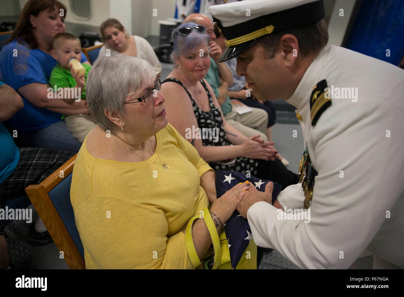 NEWPORT NEWS, Va. (May 13, 2016) -- Lt. Cmdr. Michael Stone, assigned to Pre-Commissioning Unit Gerald R. Ford (CVN 78), presents his mother, Pamela S. Stone, with the national ensign during his retirement ceremony in the ship's forecastle. Ford is the first of a new class of aircraft carriers currently under construction by Huntington Ingalls Industries Newport News Shipbuilding. (U.S. Navy photo by Mass Communication Specialist Seaman Apprentice Connor Loessin/Released) - Stock Image