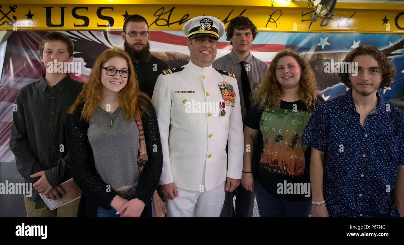 NEWPORT NEWS, Va. (May 13, 2016) --Lt. Cmdr. Michael Stone, assigned to Pre-Commissioning Unit Gerald R. Ford (CVN 78), poses with his family following his retirement ceremony in the ship's forecastle. Ford is the first of a new class of aircraft carriers currently under construction by Huntington Ingalls Industries Newport News Shipbuilding.  (U.S. Navy photo by Mass Communication Specialist Seaman Apprentice Connor Loessin/Released) - Stock Image