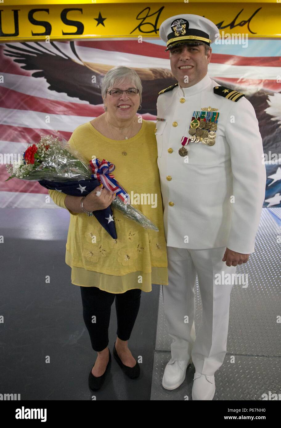 NEWPORT NEWS, Va. (May 13, 2016) --Lt. Cmdr. Michael Stone, assigned to Pre-Commissioning Unit Gerald R. Ford (CVN 78), poses with his mother, Pamela S. Stone, following his retirement ceremony in the ship's forecastle. Ford is the first of a new class of aircraft carriers currently under construction by Huntington Ingalls Industries Newport News Shipbuilding.  (U.S. Navy photo by Mass Communication Specialist Seaman Apprentice Connor Loessin/Released) - Stock Image