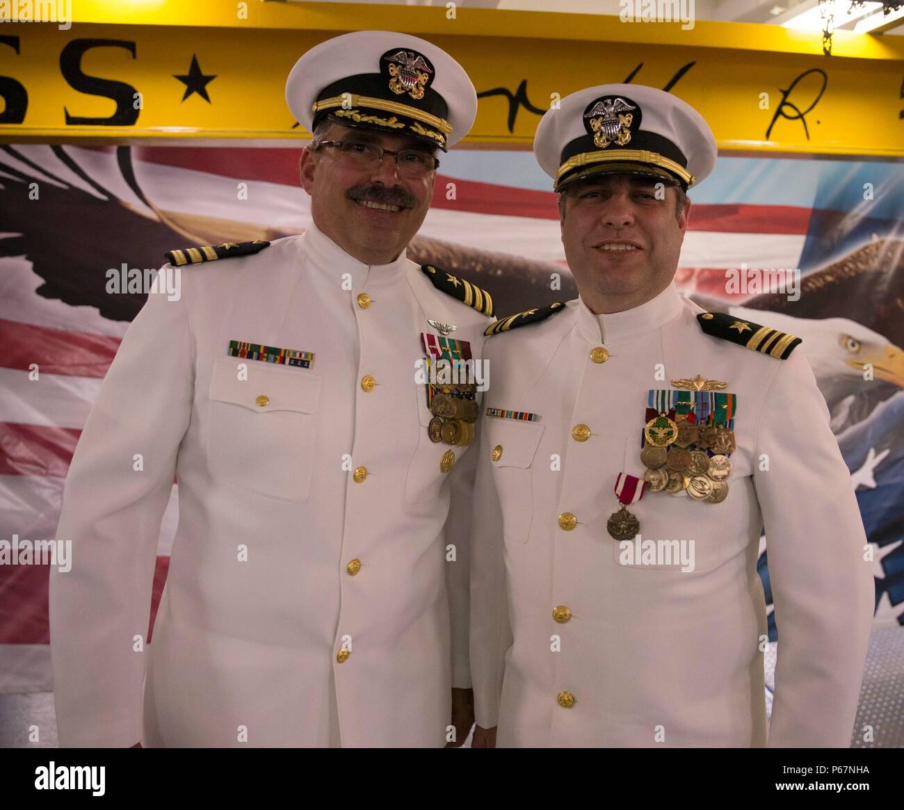 NEWPORT NEWS, Va. (May 13, 2016) --Cmdr. Gilbert Mucke, assigned to Pre-Commissioning Unit Gerald R. Ford (CVN 78), poses with his protégé, Lt. Cmdr. Michael Stone following a retirement ceremony in the ship's forecastle. Ford is the first of a new class of aircraft carriers currently under construction by Huntington Ingalls Industries Newport News Shipbuilding.  (U.S. Navy photo by Mass Communication Specialist Seaman Apprentice Connor Loessin/Released) - Stock Image