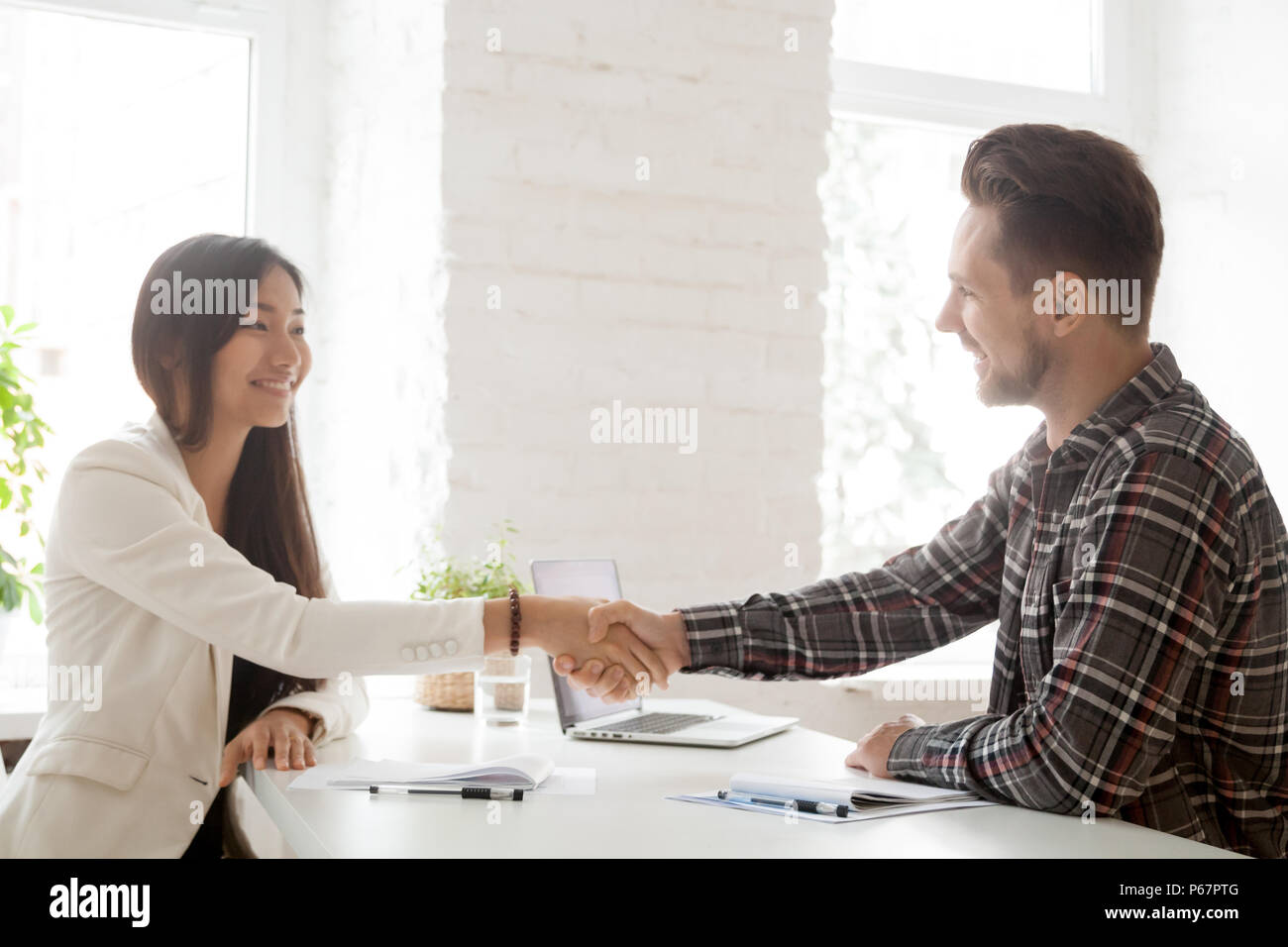 Smiling partners handshaking after successful work negotiations Stock Photo