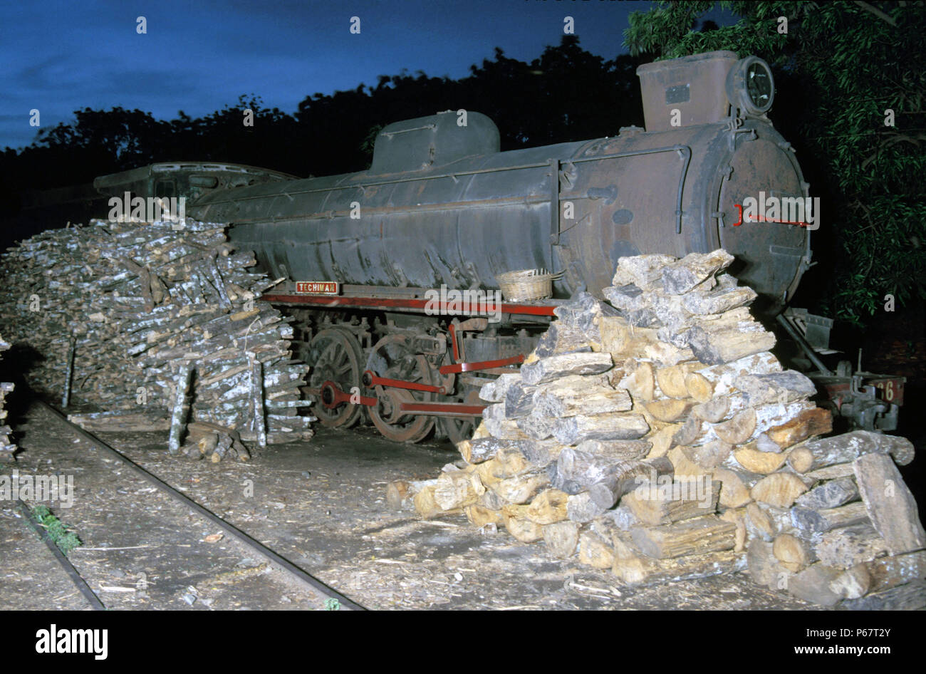 Piles of logs for lighting up steam locomotives at Accra shed Ghana. The locomotive is Vulcan Foundry 4-8-2 No.266' Techiman'. - Stock Image