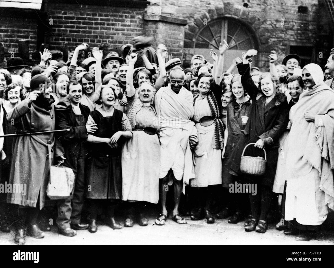 Photograph of Mahatma Gandhi being greeted by a group of female textile workers during a visit to Darwen Lancashire. Dated 1931 - Stock Image