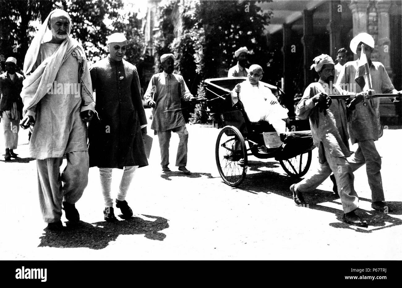 Khan Abdul Ghaffar Khan and Jawaharlal Nehru walk to a Congress meeting, while Sardar Patel is pulled alongside in a rickshaw. - Stock Image