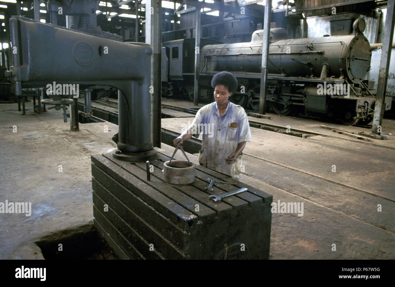The Craven cutting machine at Accra Steam sheds. Charlotte Sowah takes measurements as a Vulcan Foundry 4-8-2 complete with Giest chimney stands in th - Stock Image