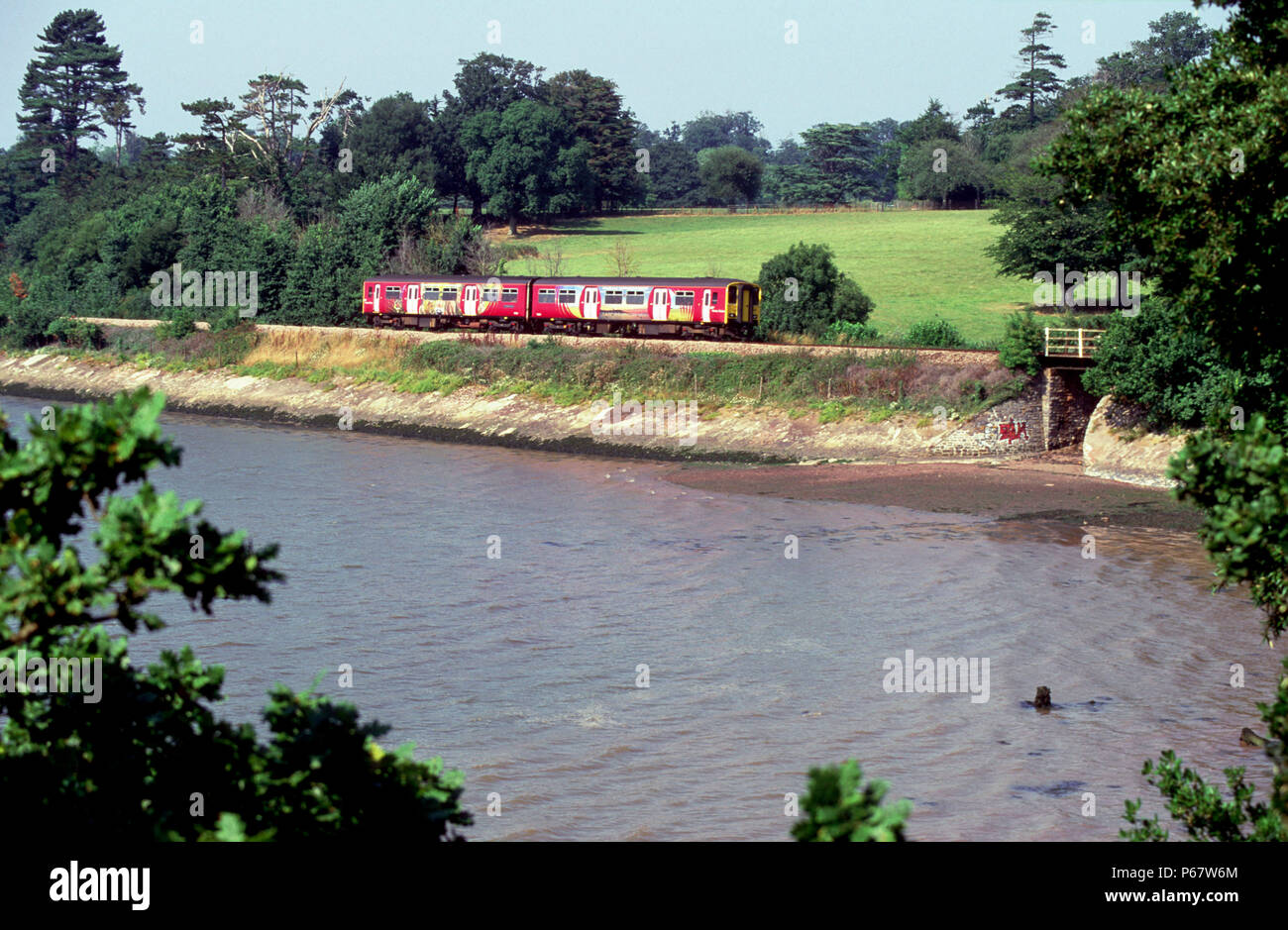 The Devon branchlines are worked by various DMU trainsets including this view of the Exmouth branch where a brightly liveried 2-car Class 150/2 skirts - Stock Image