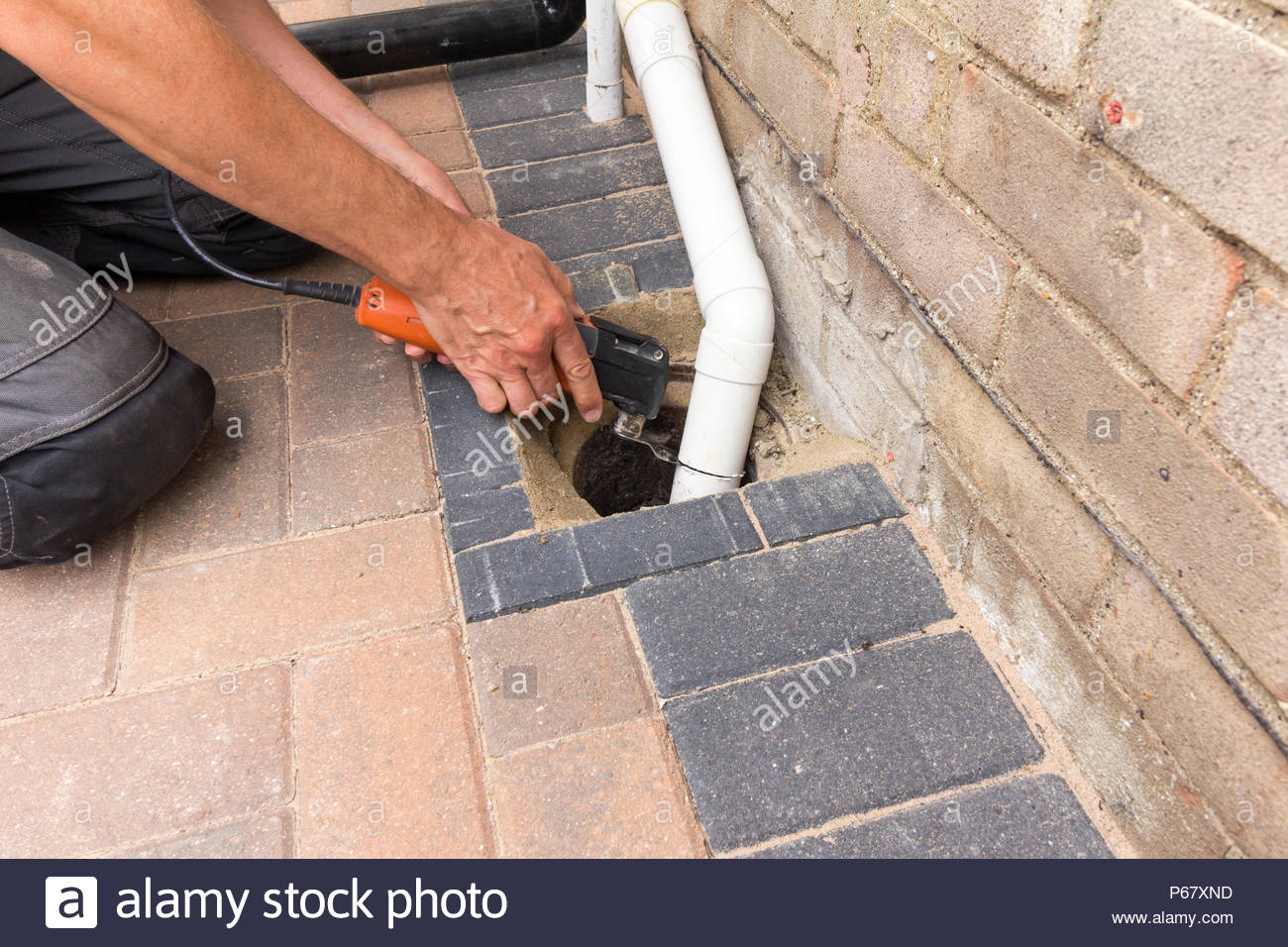Male using an oscillating saw to fix a plastic drainpipe - Stock Image