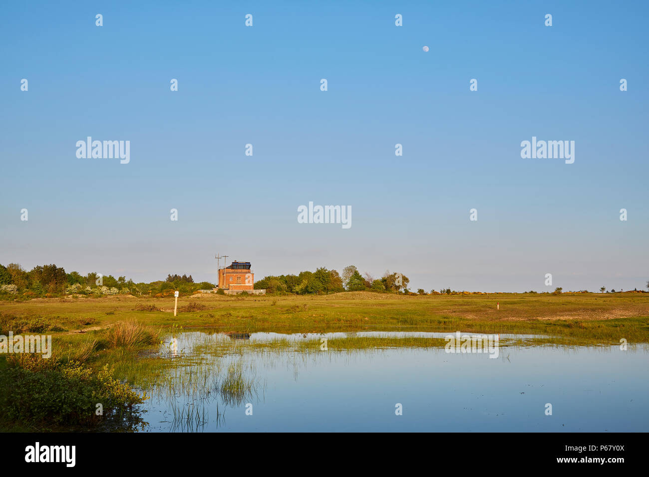 The control tower of the former RAF Greenham Common airbase taken on a clear spring evening with the moon high in the cloudless blue sky, Newbury, UK - Stock Image