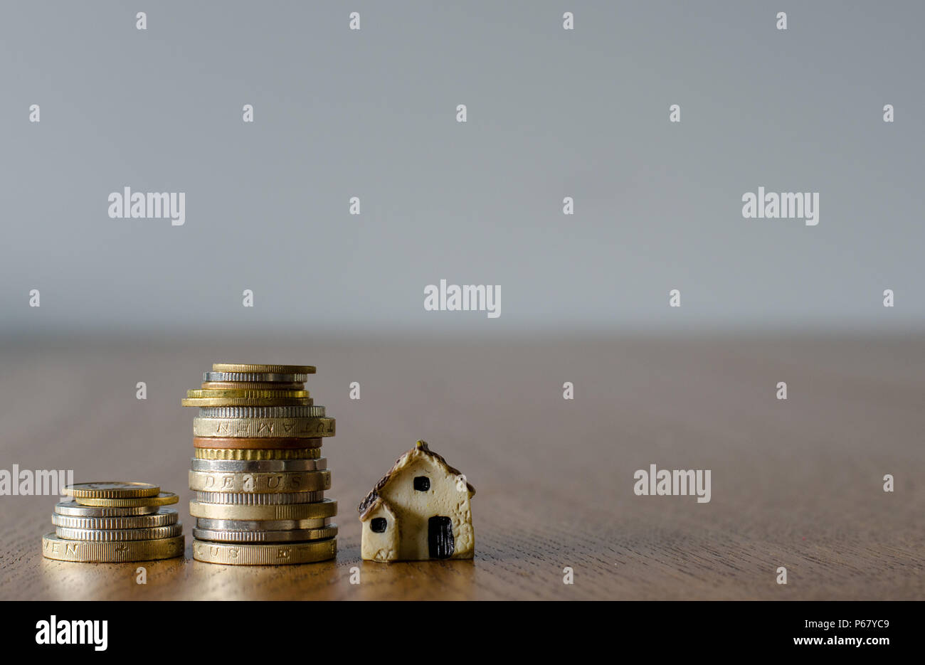 Home mortgage concept with tiny plastic house model and coins - Stock Image
