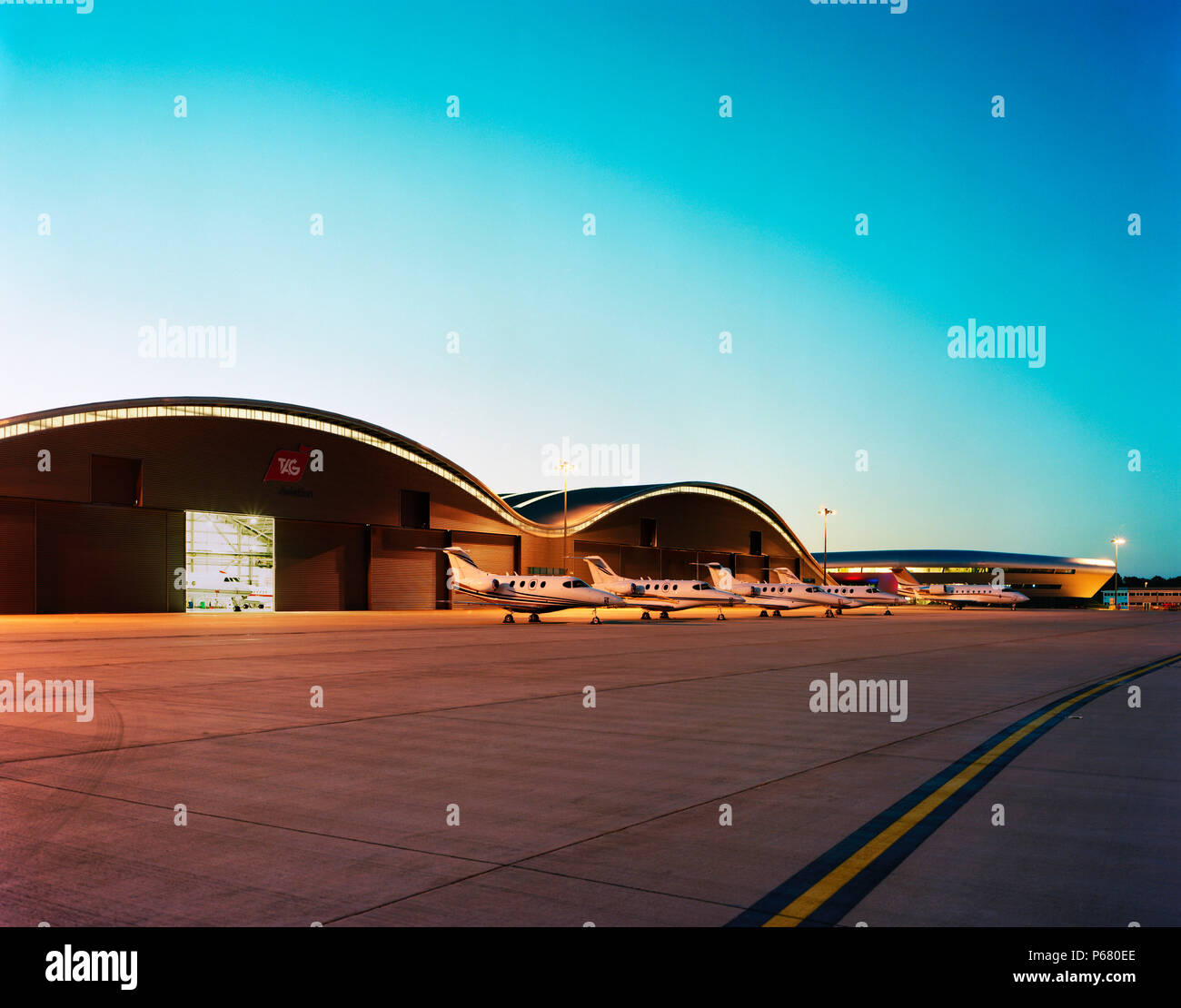 The tower of Farnborough airport and Hangars with parked airoplane. Designed by 3d reid architects. - Stock Image