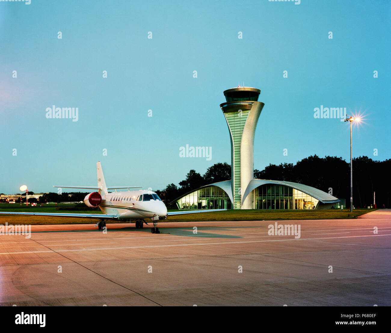 The tower of Farnborough airport with parked airoplane. Designed by 3d reid architects. - Stock Image