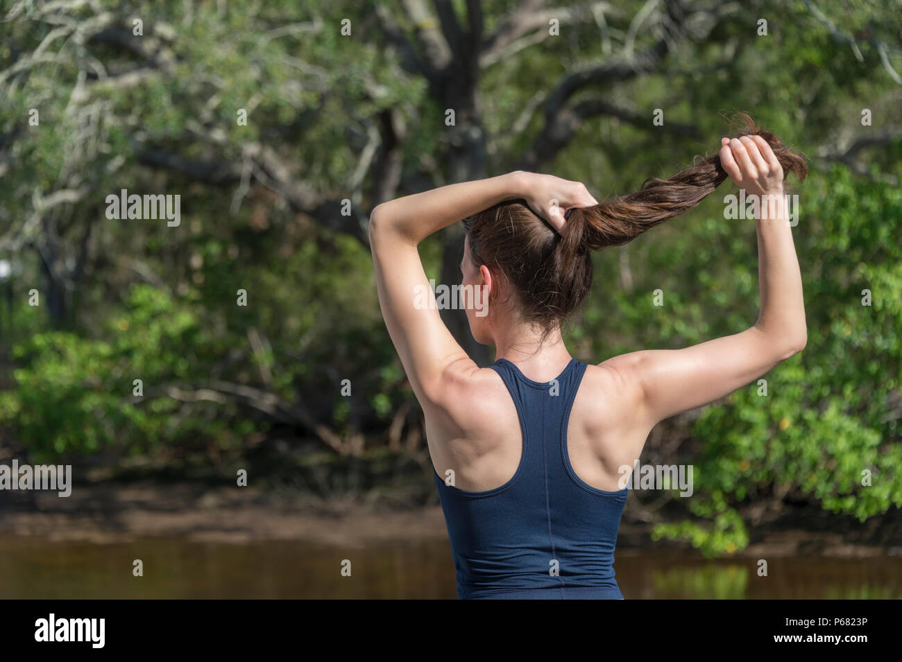 sportswoman tying her hair up before exercising outside - Stock Image