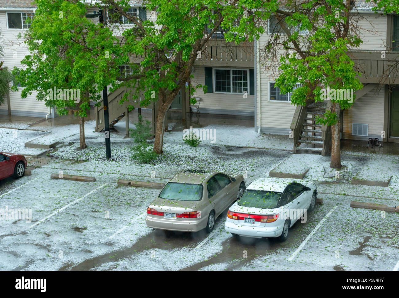 Hailstorm on parked cars of a suburban apartment building, Aurora Colorado US. Vertical streaks-(hail falling) white hail on parking area. - Stock Image