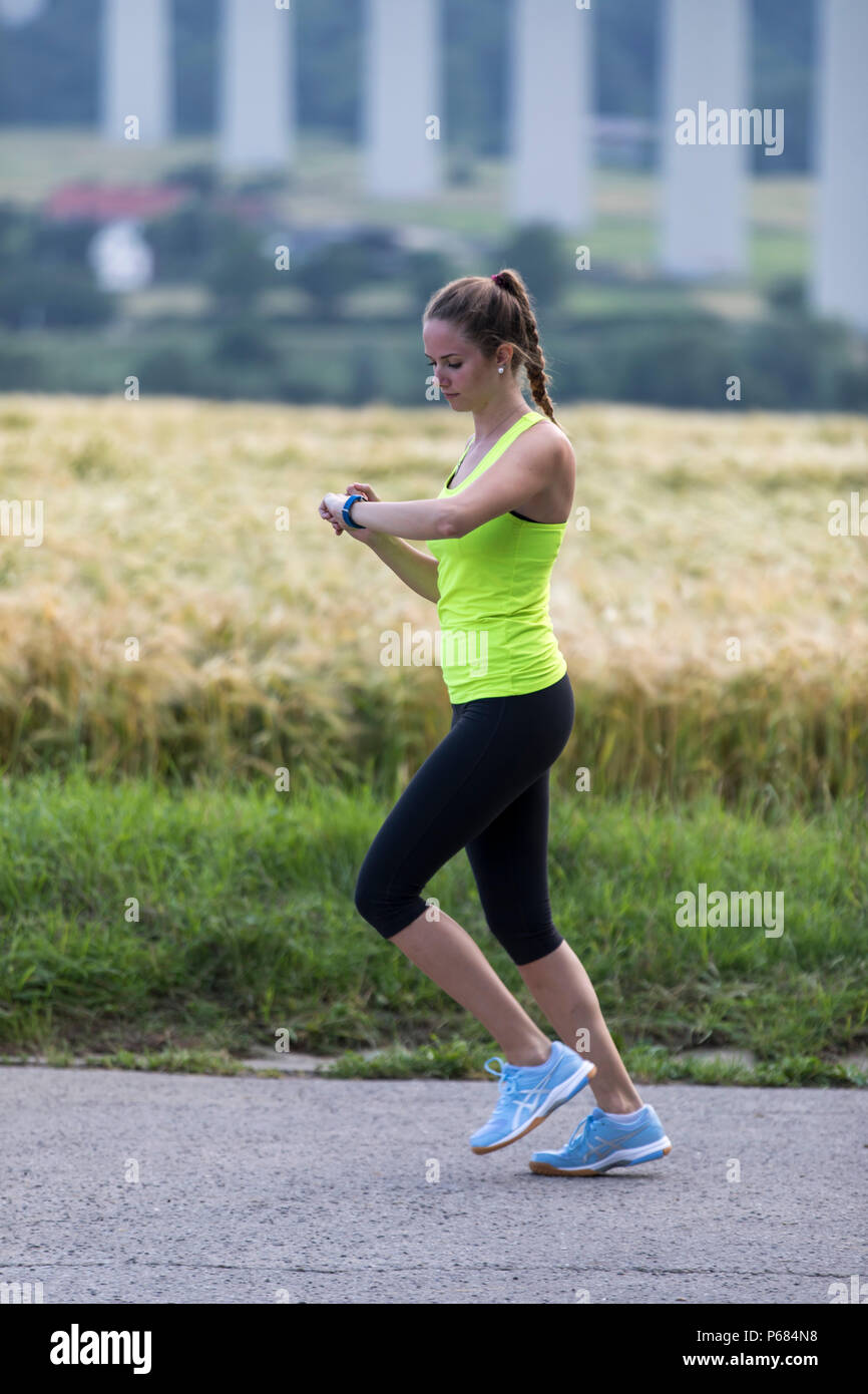 Young woman jogging, running, checking her vital signs on a fitness watch, fitness tracker, heart rate, number of steps, distance, time, calories burn - Stock Image