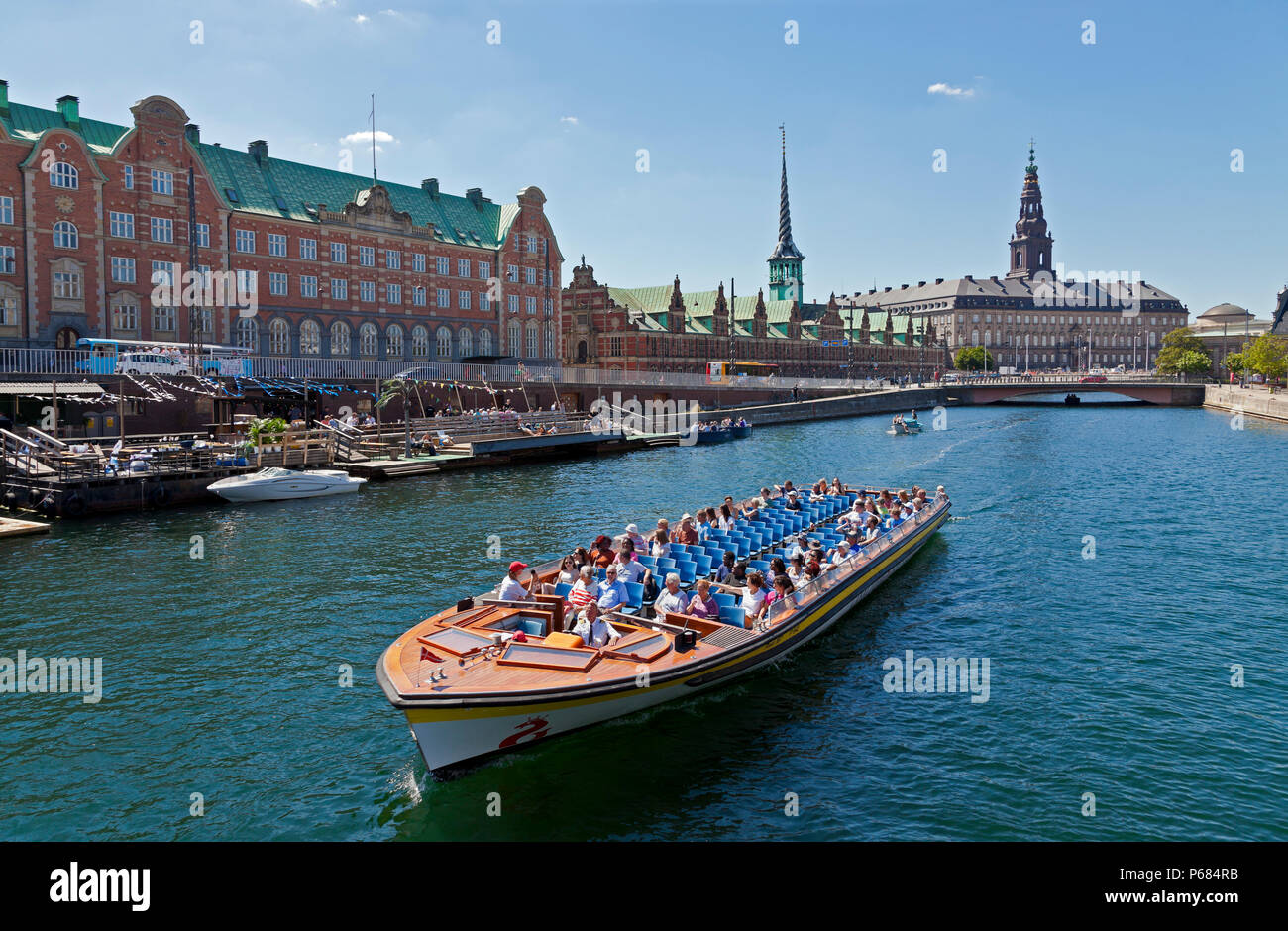 Canal cruise boat in Slotsholm Canal in Copenhagen.Christiansborg Castle, the Parliament, the old stock exchange and dockside cafe and kayak rental. Stock Photo