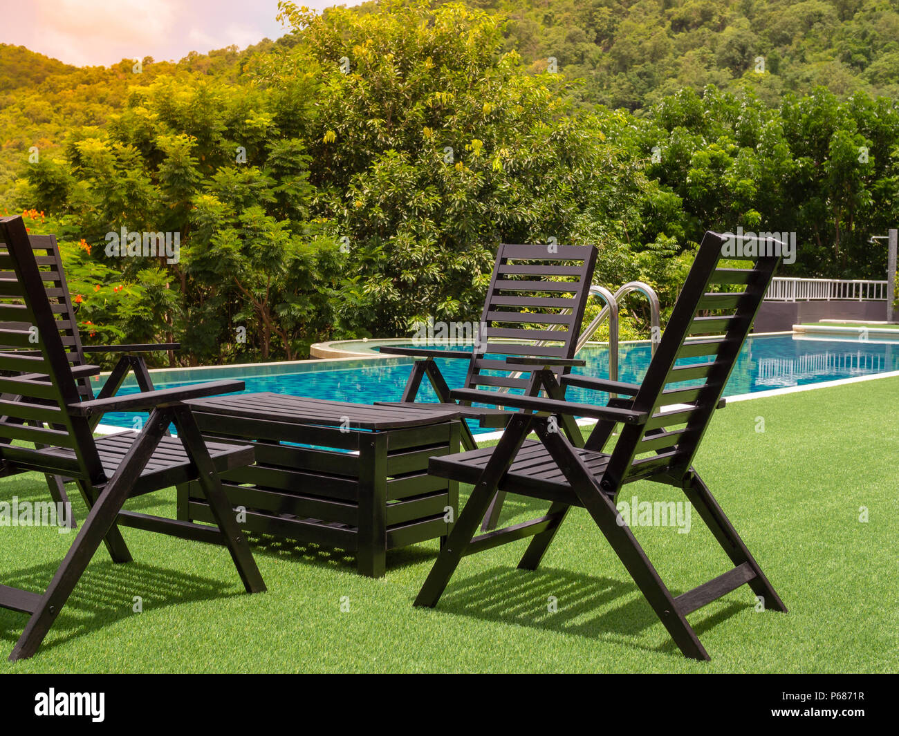 Swimming Pool With Wooden Table Set On Grass On Tree And Forest View Nature  Background.