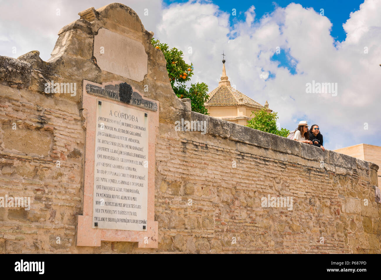 Andalucia Spain travel, two young women travelers lean over the old city wall in Cordoba (Cordova), Andalucia, Spain - Stock Image