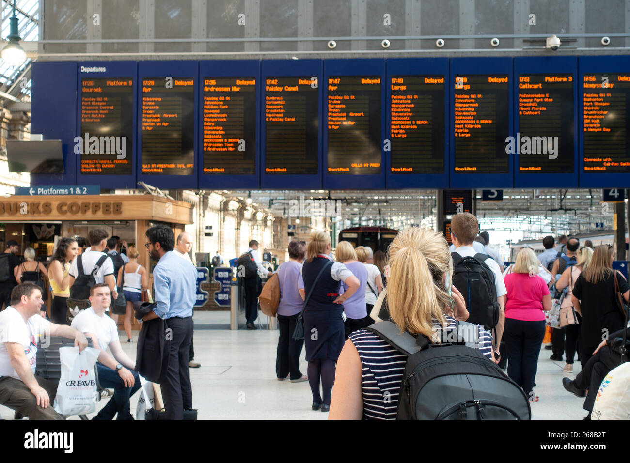 Glasgow, Scotland, UK. 28th June 2018. Passengers on the concourse of Glasgow Central Station await news of departures, after most early evening rush hour trains have been delayed or cancelled due to signalling failures or the imposition of speed restrictions. - Stock Image