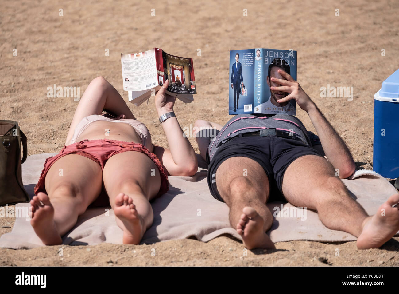 Loch Morlich, Highland, Scotland,UK. 28 June, 2018. A couple take advantage of hot weather to read on the beach at Loch Morlich near Aviemore in the Cairgorms as temperatures reached 31C the highest for many years. Credit: Iain Masterton/Alamy Live News - Stock Image