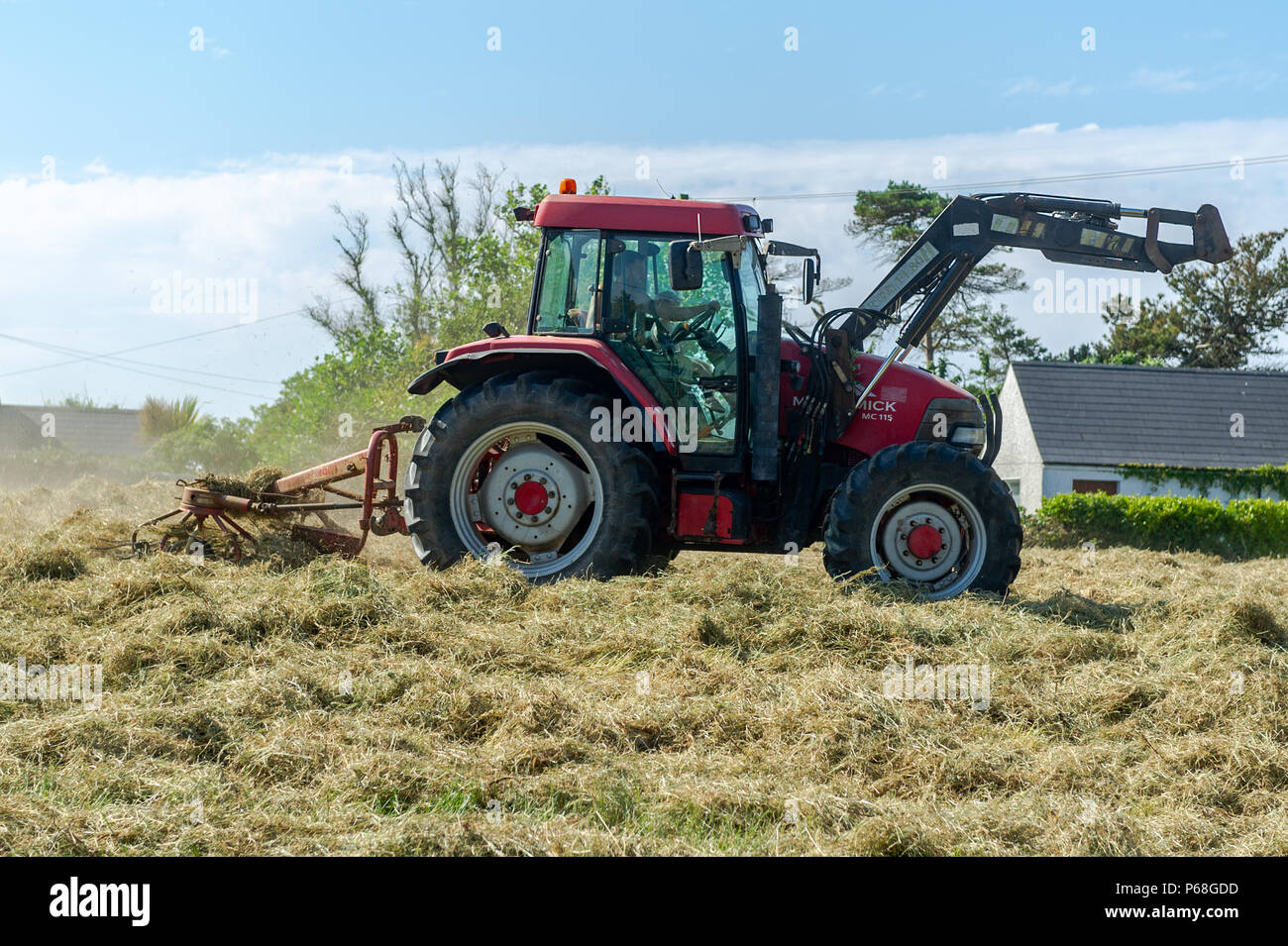Schull, West Cork, Ireland. 29th June, 2018. A farmer works on silage in his field, making the most of the dry weather whilst it lasts. Temperatures will remain in the mid 20's Celsius for the rest of the weekend but rain is forecast from Monday onwards. Credit: Andy Gibson/Alamy Live News. - Stock Image